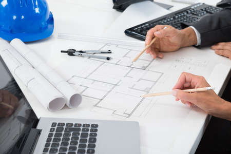 Photo pour Close-up Of Two Architects Hands Working On Blueprint - image libre de droit