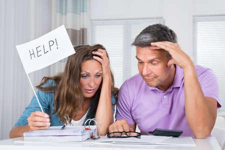 Photo pour Worried Couple Sitting In Living Room Needs Help Due To Financial Crisis - image libre de droit