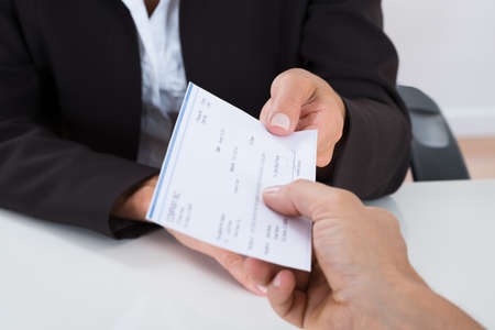 Photo pour Close-up Of Businessperson Hands Giving Cheque To Other Person At Desk - image libre de droit