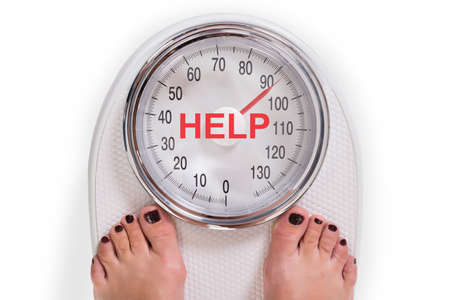 Foto de Low section of woman on weight scale with help text over white background - Imagen libre de derechos