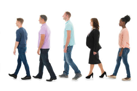 Foto de Full length side view of creative people walking with manager in row against white background - Imagen libre de derechos