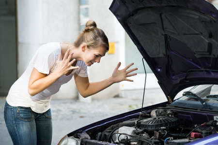 Photo pour Frustrated young woman looking at broken down car engine on street - image libre de droit