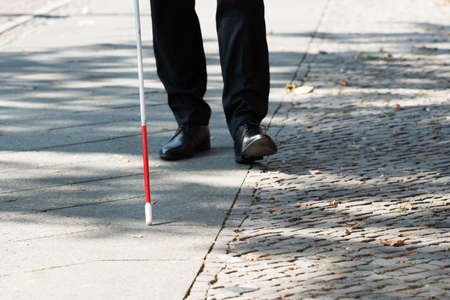 Photo pour Close-up Of A Blind Man Standing With White Stick On Street - image libre de droit