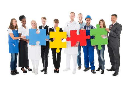 Foto de Portrait of confident people with various occupations holding jigsaw pieces while standing against white background - Imagen libre de derechos
