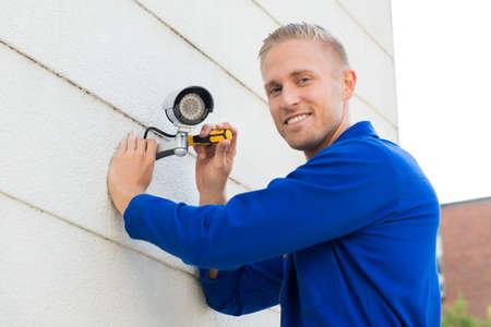 Foto de Smiling Young Technician Installing Camera On Wall With Screwdriver - Imagen libre de derechos