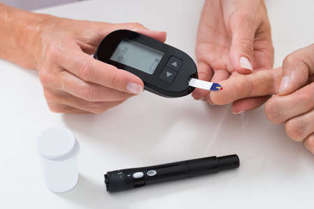 Foto per Close-up Of Doctor Measuring Sugar Reading Of Patient With Glucometer - Immagine Royalty Free