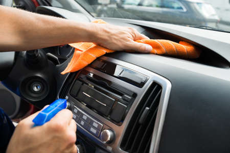 Photo pour Cropped image of mature male worker cleaning car dashboard - image libre de droit