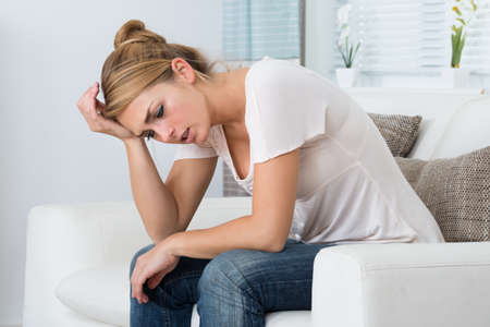 Photo pour Young stressed woman sitting in living room at home - image libre de droit
