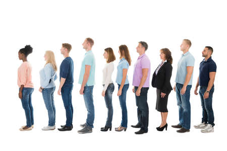 Foto de Full length side view of creative business people standing in row against white background - Imagen libre de derechos