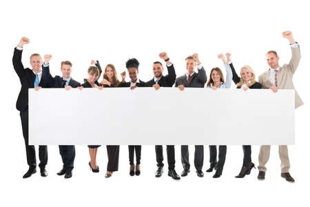 Foto de Full length portrait of business team with arms raised holding blank billboard against white background - Imagen libre de derechos