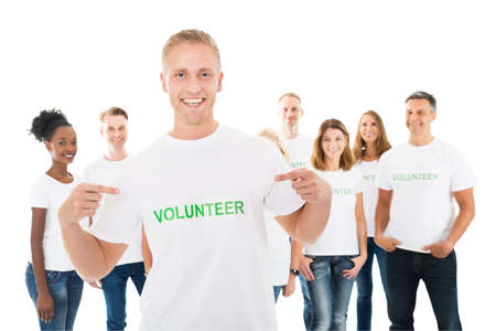 Photo for Portrait of happy man showing volunteer text on tshirt with friends standing over white background - Royalty Free Image