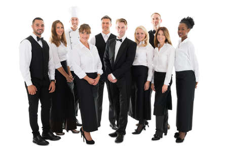 Photo for Full length portrait of confident restaurant staff standing in row against white background - Royalty Free Image