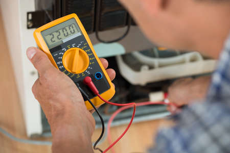 Photo pour Cropped image of male repairman checking fridge with digital multimeter at home - image libre de droit