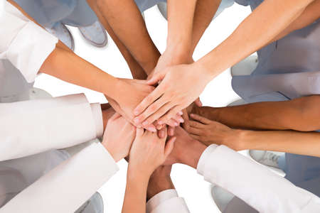 Photo pour Directly above shot of medical team standing hands against white background - image libre de droit