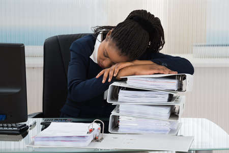 Photo pour Young African Businesswoman Sleeping On Stacked Of Files - image libre de droit