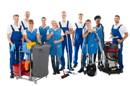 Photo pour Portrait of happy janitors with cleaning equipment standing against white background - image libre de droit