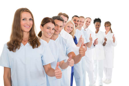 Portrait of confident medical team showing thumbs up while standing in line against white background