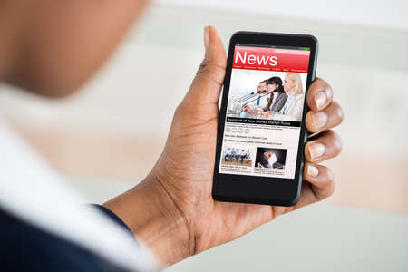 Photo for Close-up Of A Woman's Hand Reading News On Mobile Phone - Royalty Free Image