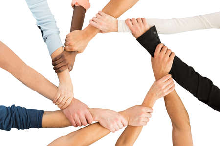 Photo pour Directly above shot of people holding each other's hand in showing unity against white background - image libre de droit