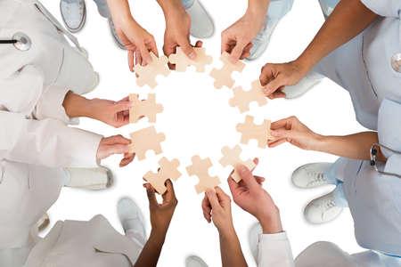 Foto de Directly above shot of medical team holding blue jigsaw pieces in huddle against white background - Imagen libre de derechos