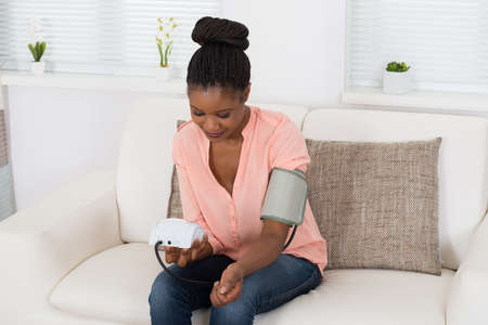 Foto per Young African Woman Checking Blood Pressure At Home - Immagine Royalty Free