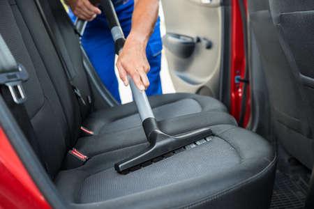 Foto de Handyman vacuuming car back seat with vacuum cleaner - Imagen libre de derechos