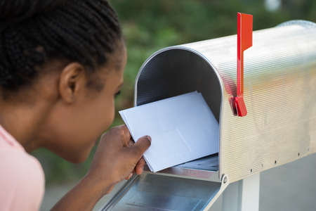 Photo pour Close-up Of Woman Putting Letter In Mailbox - image libre de droit