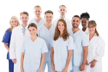 Photo pour Portrait of happy multiethnic medical team standing against white background - image libre de droit