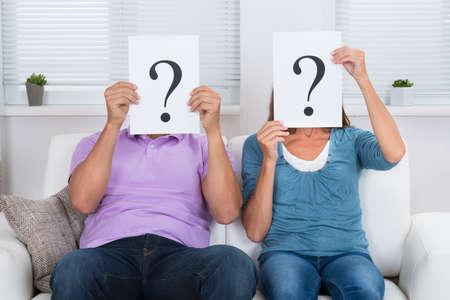 Photo pour Couple Together Sitting On Sofa Hiding Face With Question Mark Sign - image libre de droit