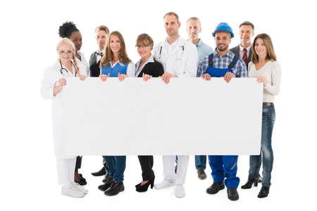 Foto de Group portrait of people with various occupations holding blank billboard against white background - Imagen libre de derechos