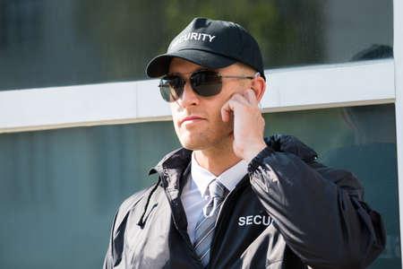 Foto de Close-up Of Security Guard Standing In Front Of The Entrance Listening To Earpiece - Imagen libre de derechos