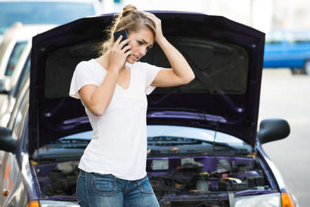 Foto de Young woman using mobile phone while looking at broken down car on street - Imagen libre de derechos