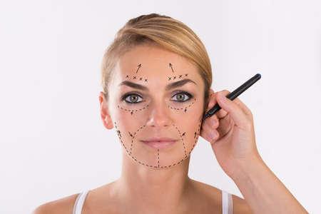 Photo pour Portrait of young woman undergoing facelift surgery over white background - image libre de droit