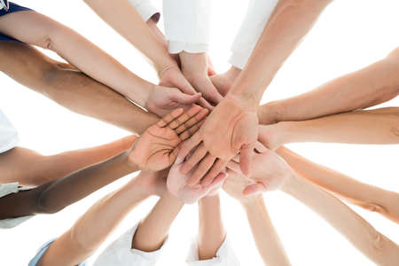 Photo for Directly below shot of medical team piling hands against white background - Royalty Free Image