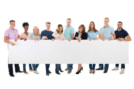Photo for Full length portrait of confident creative business team holding blank billboard against white background - Royalty Free Image
