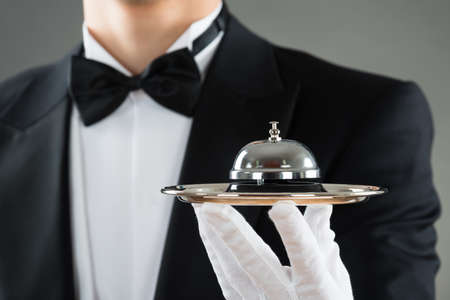 Photo pour Midsection of waiter holding service bell in plate against gray background - image libre de droit