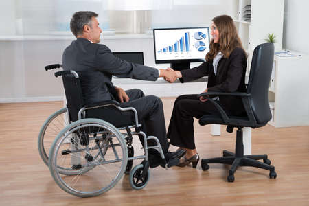 Foto de Happy Businesswoman Shaking Hands With Disabled Businessman In Office - Imagen libre de derechos