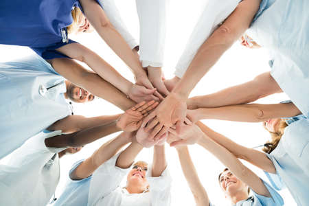 Photo pour Directly below shot of multiethnic medical team stacking hands over white background - image libre de droit
