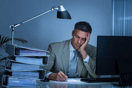 Photo for Tired businessman with hand on face writing on document while working late in office - Royalty Free Image