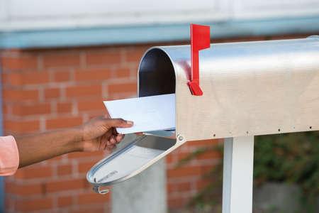 Foto de Close-up Of Person's Hand Putting Letters In Mailbox - Imagen libre de derechos