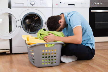 Foto de Exhausted young man with laundry basket sitting on floor by washing machine at home - Imagen libre de derechos