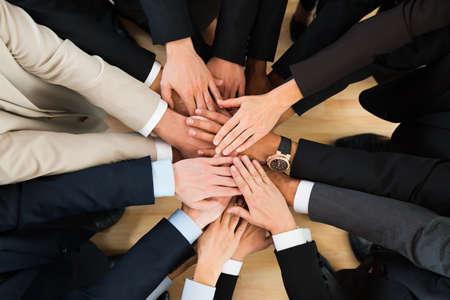 Foto de Directly above shot of business team stacking hands in office - Imagen libre de derechos