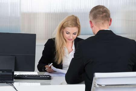 Photo pour Young businesswoman interviewing job applicant at desk in office - image libre de droit