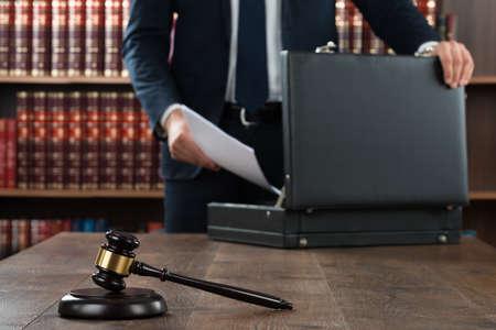 Foto de Midsection of lawyer putting documents in briefcase with gavel at desk in courtroom - Imagen libre de derechos