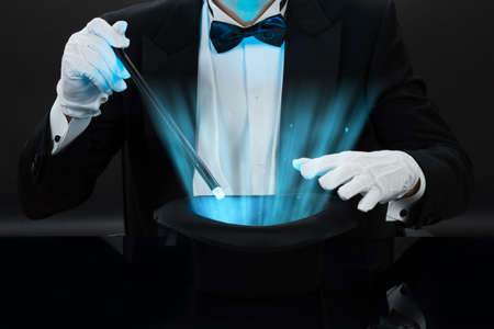 Photo for Midsection of magician holding magic wand over illuminated hat against black background - Royalty Free Image