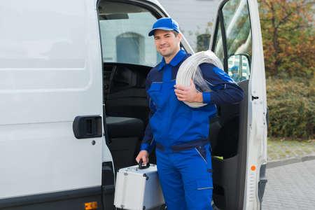 Foto für Portrait of confident technician with cable coil and toolbox standing outside van - Lizenzfreies Bild