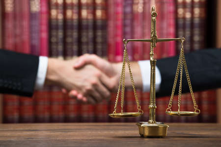 Photo pour Justice scale on wooden table with judge and client shaking hands in background at courtroom - image libre de droit