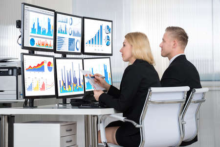 Photo for Young financial analysts using computers at desk in office - Royalty Free Image