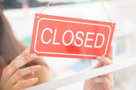 Photo pour Closeup of female owner holding closed sign in clothing store - image libre de droit
