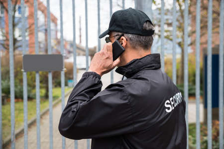 Foto de Confident mature security guard talking on mobile phone in front of gate - Imagen libre de derechos